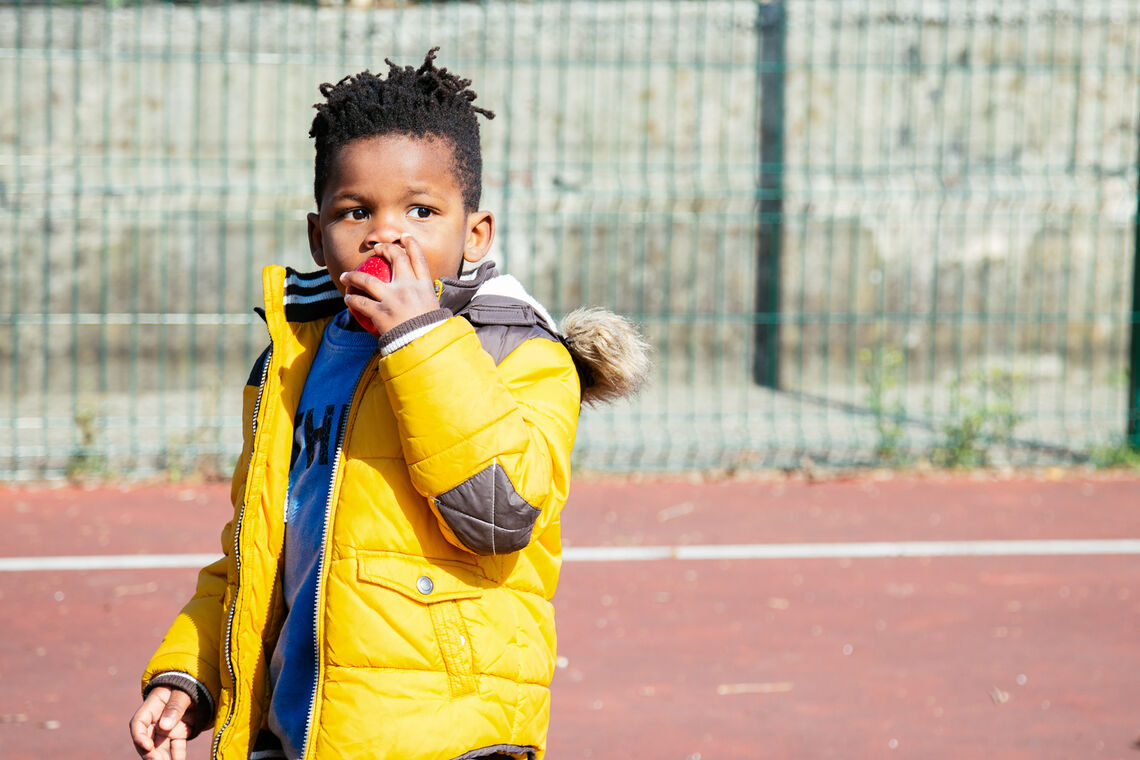 boy eating apple outside of school wearing a coat looking worried