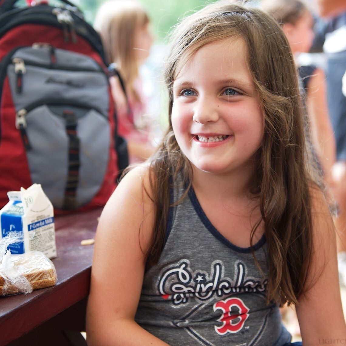 Little girl smiling at a picnic table with lunch at Summer Eats site