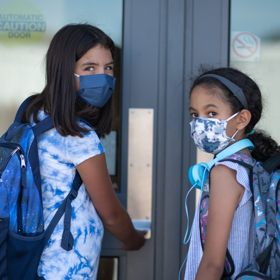 Two middle school aged girls in masks are wearing backpacks, looking over their shoulders at camera walking into front doors