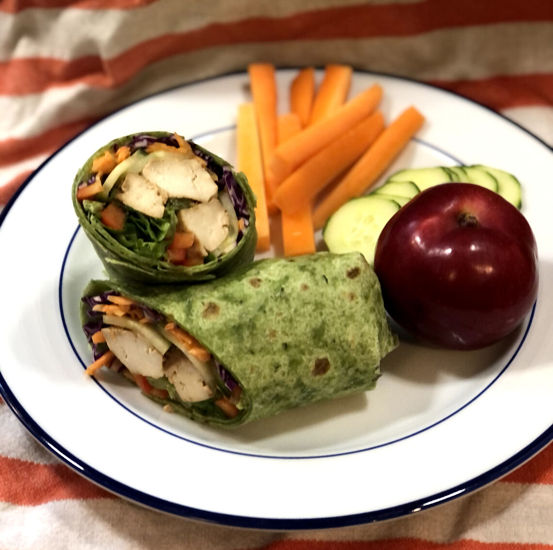 Baked soy ginger tofu served in a wrap with a fresh side of cut veggies and an apple.
